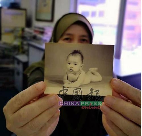 中国侨网哈丝玛手中这张逾半世纪的泛黄婴儿照,成了她寻回亲生家人的唯一线索。(马来西亚《中国报》)