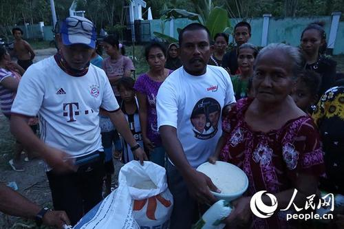中国侨网接受中国志愿者救援物资的当地灾民