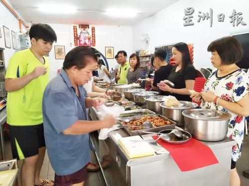 中国侨网许瑞安(左)主厨开业了34年,每天傍晚开档,前来打包晚餐便菜的家庭主妇,站得满满。(马来西亚《星洲日报》)
