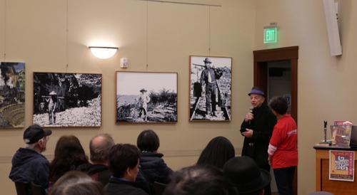 中国侨网画家佩里介绍他的三幅作品。(美国《世界日报》/梁雨辰 摄)