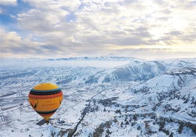 中国侨网热气球飞过被白雪覆盖的卡帕多奇亚上空。   新华社记者 邹 乐摄