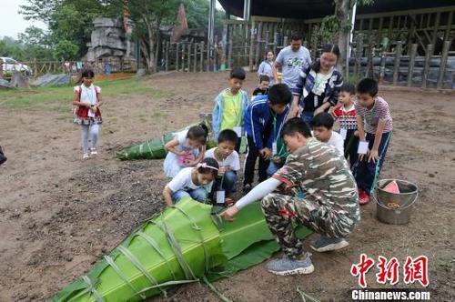 中国侨网图为饲养员与小朋友一起给非洲象包粽子。 韩璐 摄