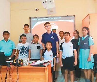 中国侨网许安(中)和学生们在一起。(图片来源:《人民日报海外版》)