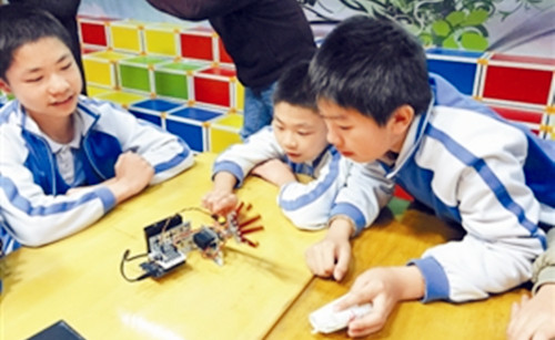 3月10日下午,(广东省)深圳市梅丽小学的机器人课堂,20位年级学生正抬着头看台上播放的机器人短片《萝卜太辣》,短片中的小机器人移动、翻身、旋转、投球流畅的动作激起同学们的阵阵惊呼。   同学们知道为什么直立行走的机器人很难研制出来吗?短片结束后,授课老师李赞拿出两个小机器人样品给孩子们研究,并介绍机器人的相关知识。随后,李赞拿出他带来的三套零件,让同学们合作组装出自己的机器人。见识过老师带来的成品,跃跃欲试的孩子们离开座位,小脑袋凑在一起,叽叽喳喳地研究这些新奇的零件,学校的科学老师也加入了动