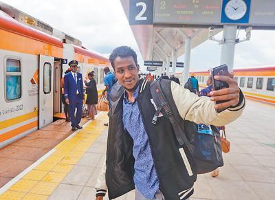 中国侨网在肯尼亚蒙内铁路内罗毕南站,一名乘客在列车前自拍。本报记者 王云松摄
