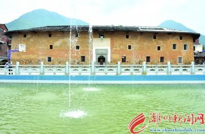 中国侨网古老的泰华楼前是现代喷泉,新农村建设与保护民族传统文化在此相融相衬。