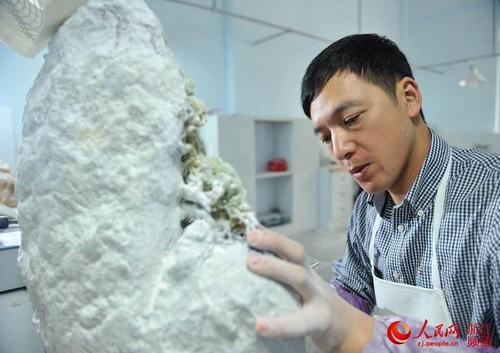 中国侨网刘宙正在制作青田石雕。