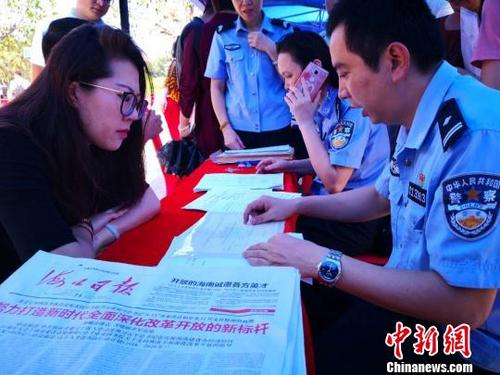 中国侨网2018年5月14日,海口公安民警在海口市三角池公园为民众办理落户手续、提供落户咨询服务。 尹海明 摄