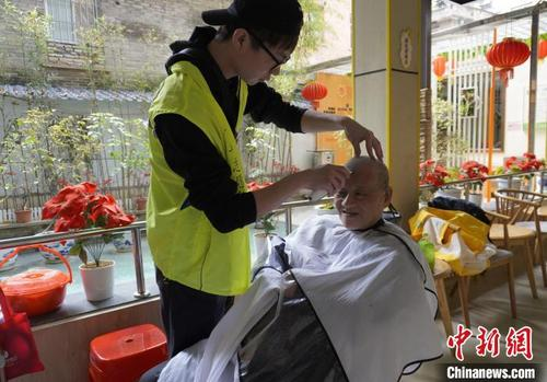 中国侨网林扬杰为老人义剪。 彭莉芳 摄