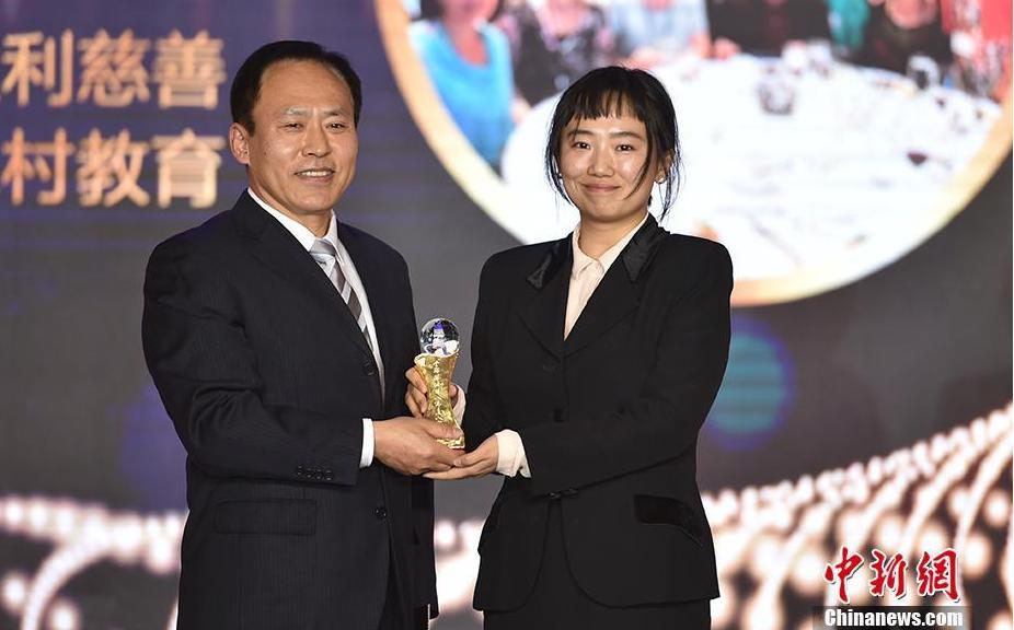 中国华文教育基金会秘书长于晓(左)为欣欣教育基金会义工团队颁奖