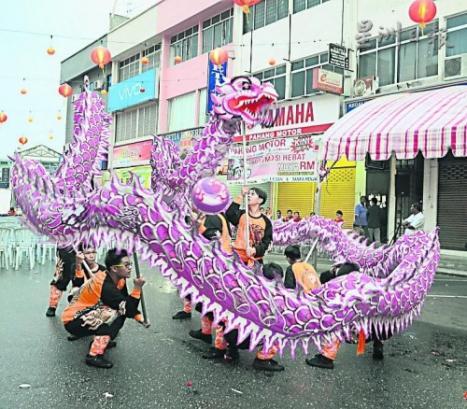游行沿途中有舞龙表演助兴。(马来西亚《星洲日报》)