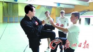 袁师傅(左)在给外国小徒弟教拳。