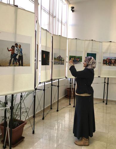 中国侨网一位摩洛哥妇女仔细观看摄影作品
