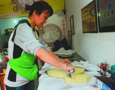 中国侨网薛福泉的爱人林颖正在切黄米糕。