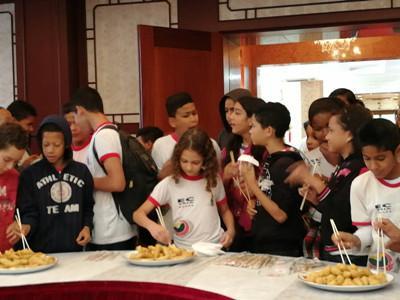 中国侨网巴西小学生在开放日活动品尝中国美食。