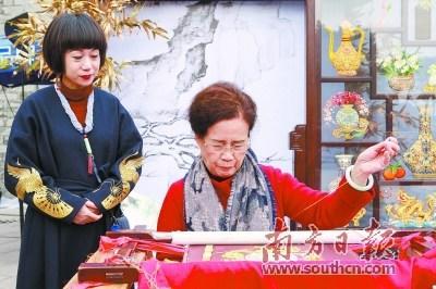 中国侨网潮州广济楼前,康惠芳展示潮绣技艺。南方日报记者 苏仕日 摄