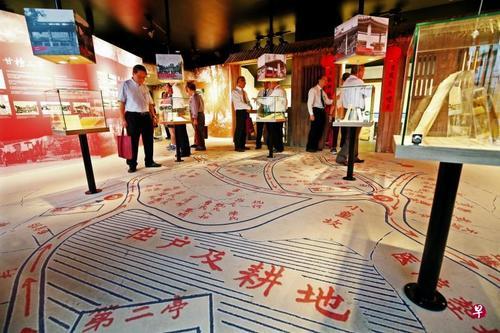 中国侨网策展人将广惠肇碧山亭文物馆的地板贴上昔日甘榜山亭的地图,构思巧妙,展览也透过媒体、实物和照片方式呈现昔日甘榜山亭的生活。(新加坡《联合早报》/梁麒麟摄)