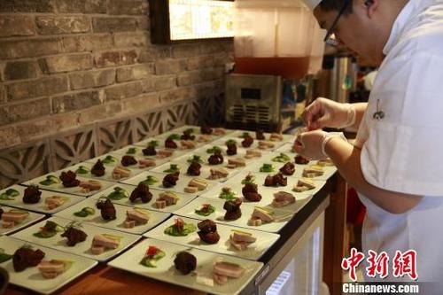 中国侨网无锡君来酒店管理集团的高级厨师精心制作代表中国江南特色的菜品。林丹摄