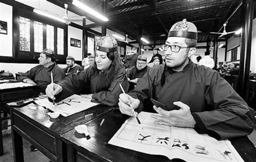 中国侨网参加世俱杯的国际排联官员们在三味书屋学书法。