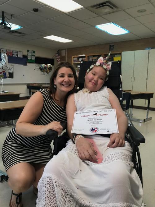 阿妮雅领到毕业证书后,与五年级老师奥尔尼(Desiree Oneil)合影。(美国《世界日报》)