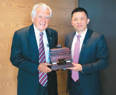 图为陈玉树(右)向澳大利亚前总理霍克(左)赠送木雕作品《君子和平鼎》。