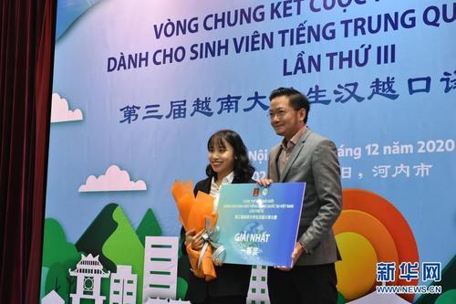 12月13日,在越南首都河内举行的第三届越南大学生汉越口译大赛决赛现场,冠军阮氏明书(左)接受颁奖。新华社记者 蒋声雄 摄