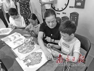 国家级非遗项目(潮阳剪纸)省级传承人郑少燕现场教授孩子剪纸。 杨可 摄