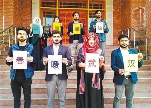 """巴基斯坦萨戈达大学孔子学院师生打出""""中国加油""""""""武汉加油""""""""巴铁与你同在""""等内容的标语,并录制视频支持中国。本报记者 梁桐 摄"""