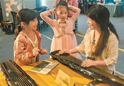 中国侨网会展现场,小朋友对古琴演奏充满了好奇。